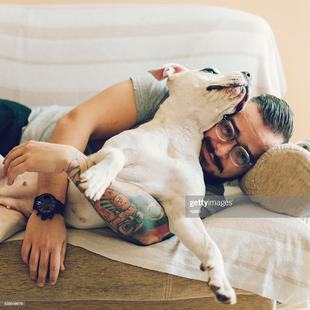 Man with tattoo embracing his dog. : Stock Photo
