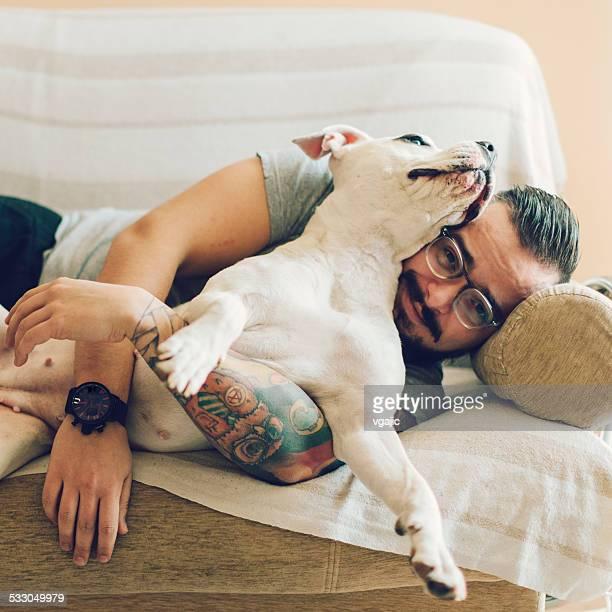 Mann mit tattoo umarmen seinem Hund.