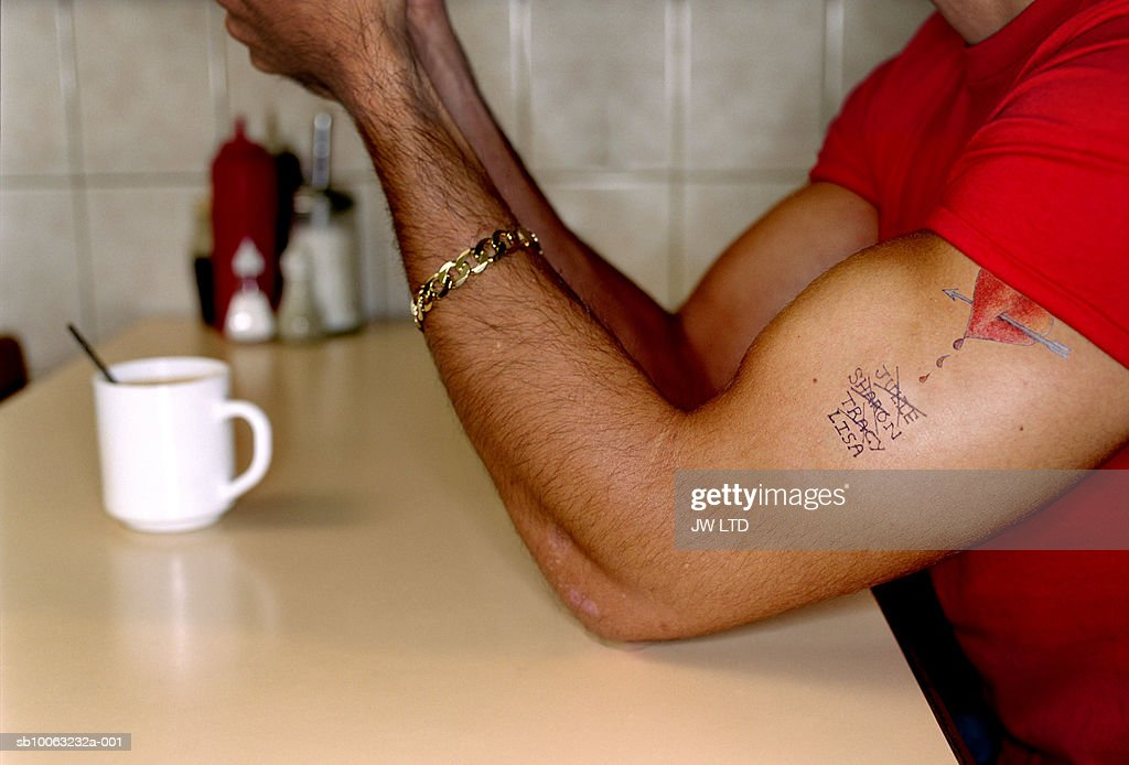 Man with tattoo in cafe : Stock Photo