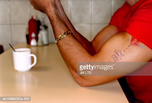 Man with tattoo in cafe : Bildbanksbilder