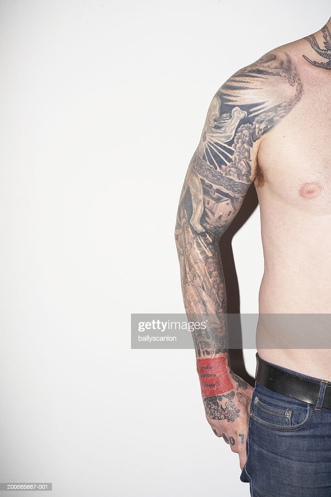 Man with tattooed arm and neck, against white background : Stock Photo