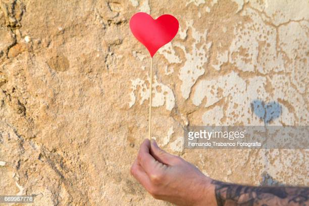 Man with tattooed arm Holding a red heart for your lover on Valentine's Day