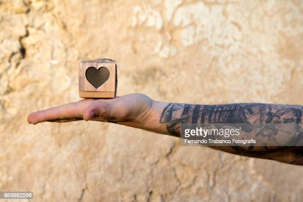 Man with tattooed arm holds in his hand a small cardboard box with love