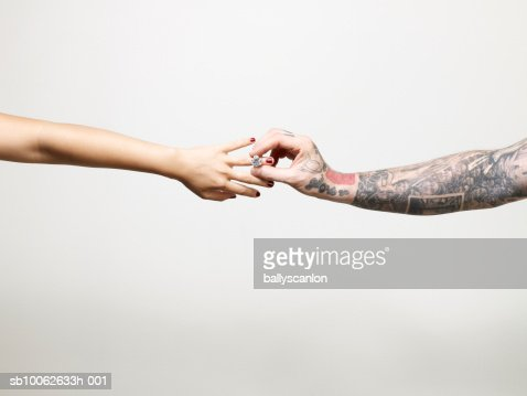 Man with tattooed arm placing ring on finger of young woman, close-up of arms and hands
