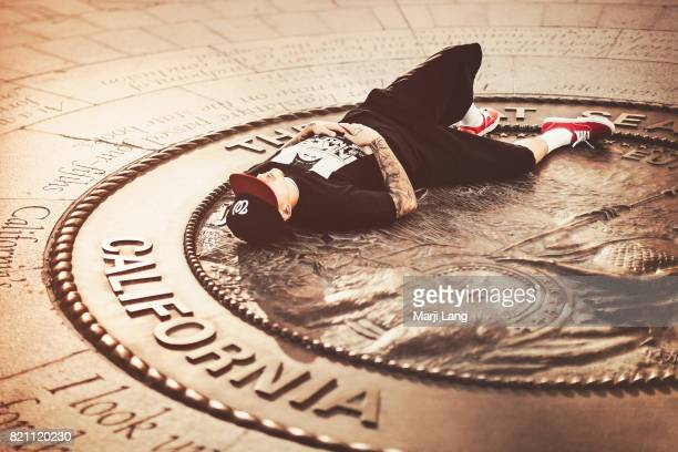 Man with tattoos lying down on the golden California symbol and text sculpted in bronze on the ground in downtown San Jose California USA