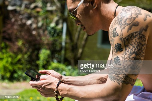 Man with tattoos using smartphone : Stock Photo