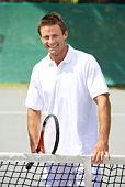 Man with tennis racquet standing by net