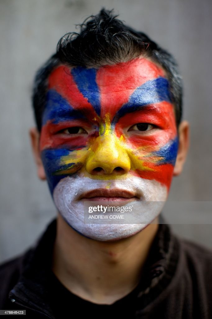 A man with the Tibetan flag painted on his face is pictured during a Free Tibet rally outside Downing Street in London on March 15, 2014. The annual march marks the anniversary of Tibetans' uprising against Chinese rule on March 10, 1959. AFP PHOTO/ANDREW COWIE