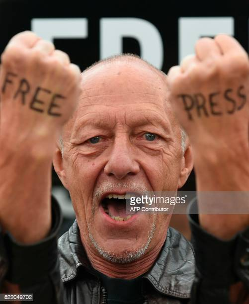A man with the words 'free press' written on the backs of his hands protests alongside Amnesty International activists and partners outside the...