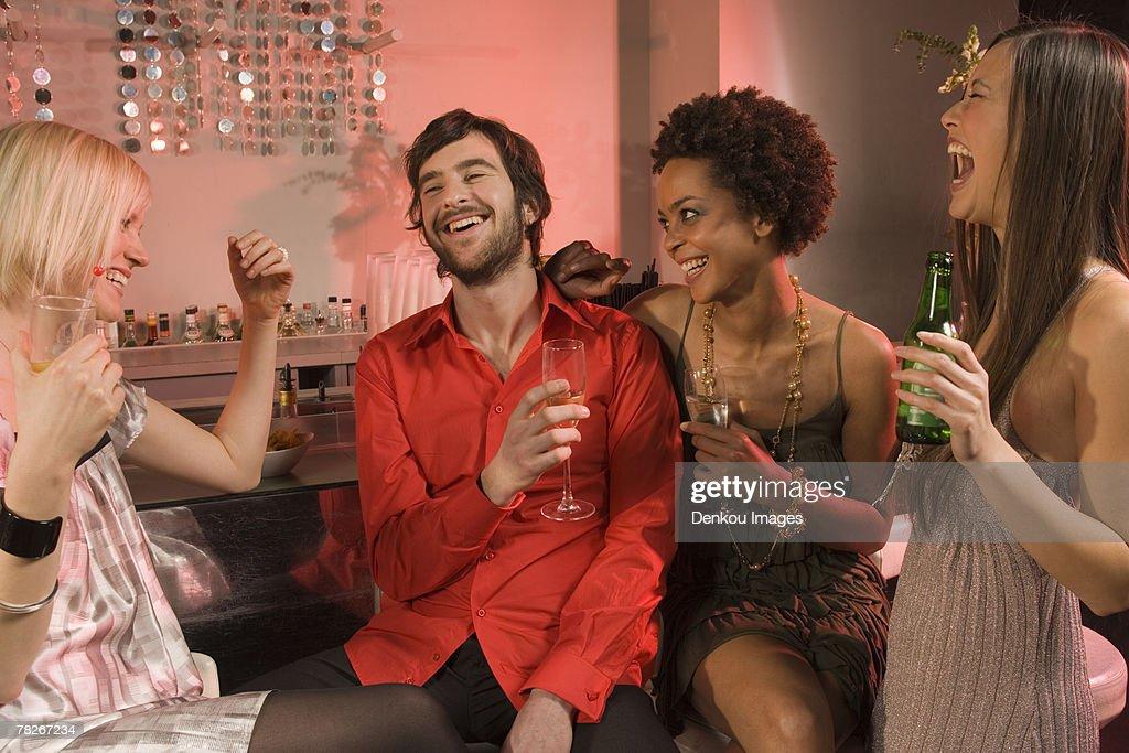 Man with three women at a nightclub. : Stock Photo