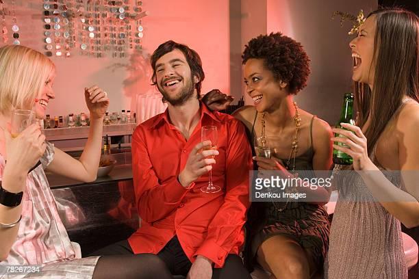 Man with three women at a nightclub.