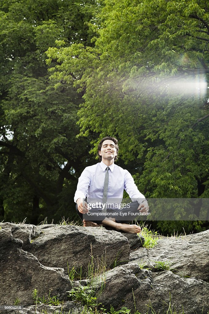 man with tie sitting with legs crossed on rock