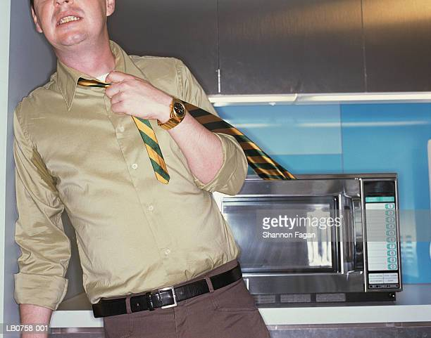 Man with tie stuck in microwave