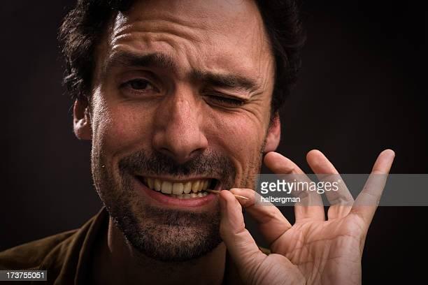 Homme avec Cure-dent à la bouche