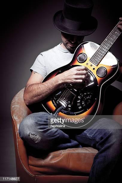 Homme jouant de la guitare avec chapeau