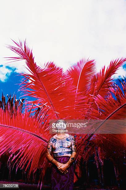 Man with traditional tattoos under palm tree