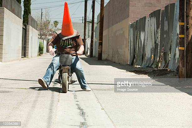 Man with traffic cone on head, riding motorbike