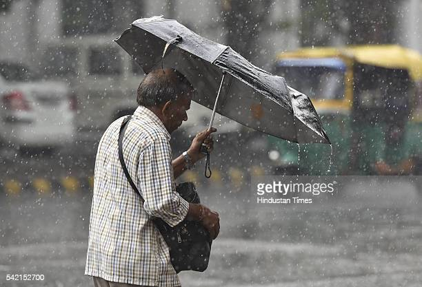 A man with umbrella cought in heavy showers at Connaught Place on June 22 2016 in New Delhi India A sudden spell of rain brought the temperatures...