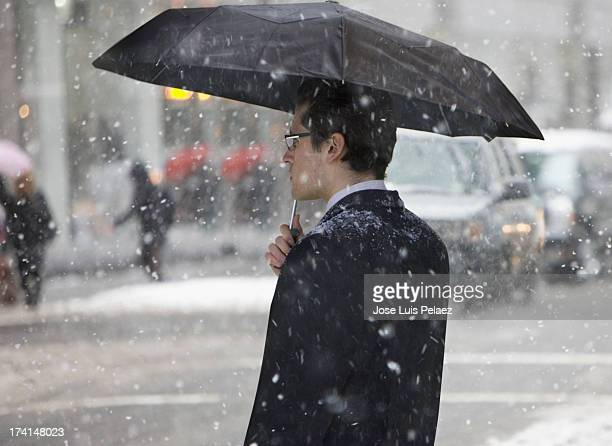 Man with umbrella crossing street in the snow