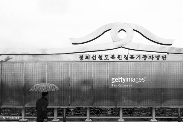 Man with umbrella in front of board with names in Korean