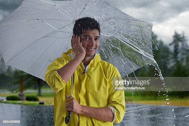 Man with umbrella talking on mobile phone