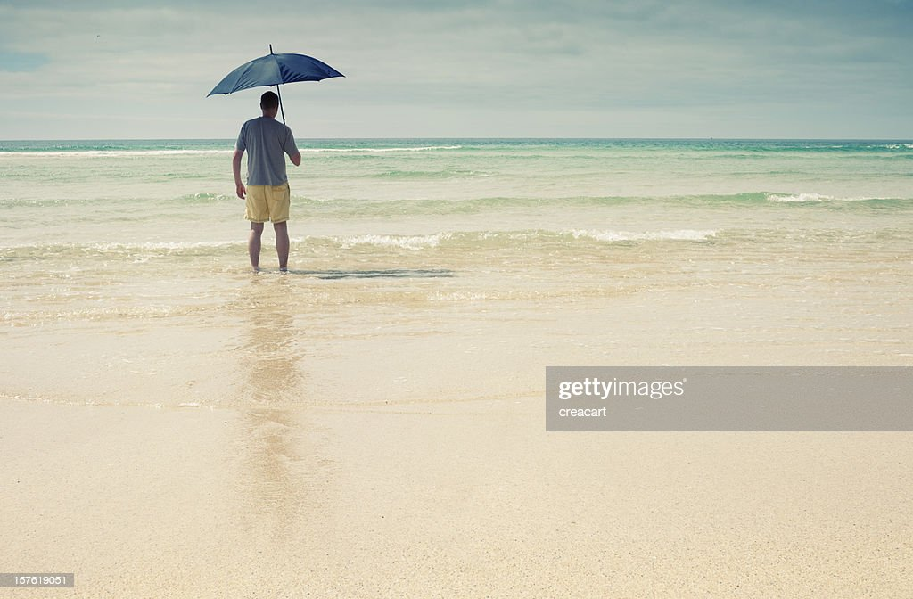 Man with Umbrella walking into the sea