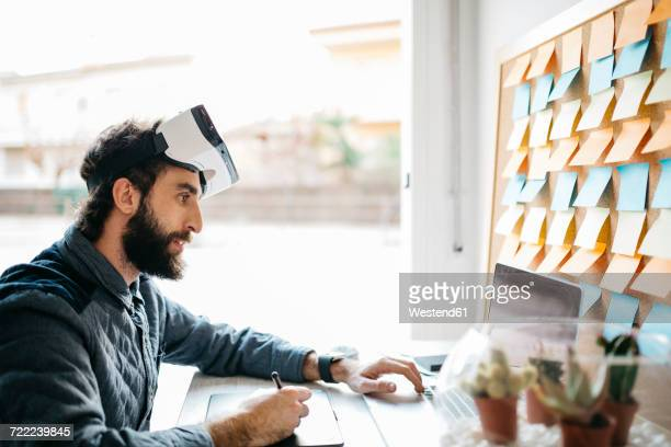 Man with Virtual Reality Glasses working working with graphics tablet and laptop at his office