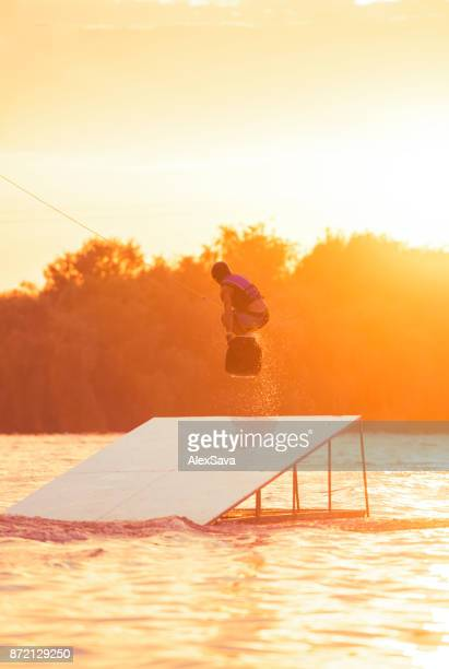 Man with wakeboard jumping in midair off ramp