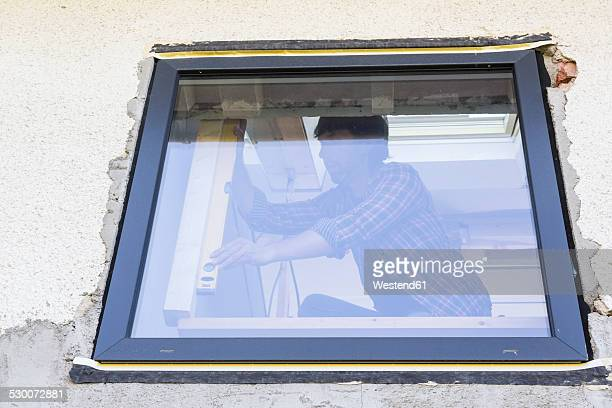 Man with water level at window during house renovation