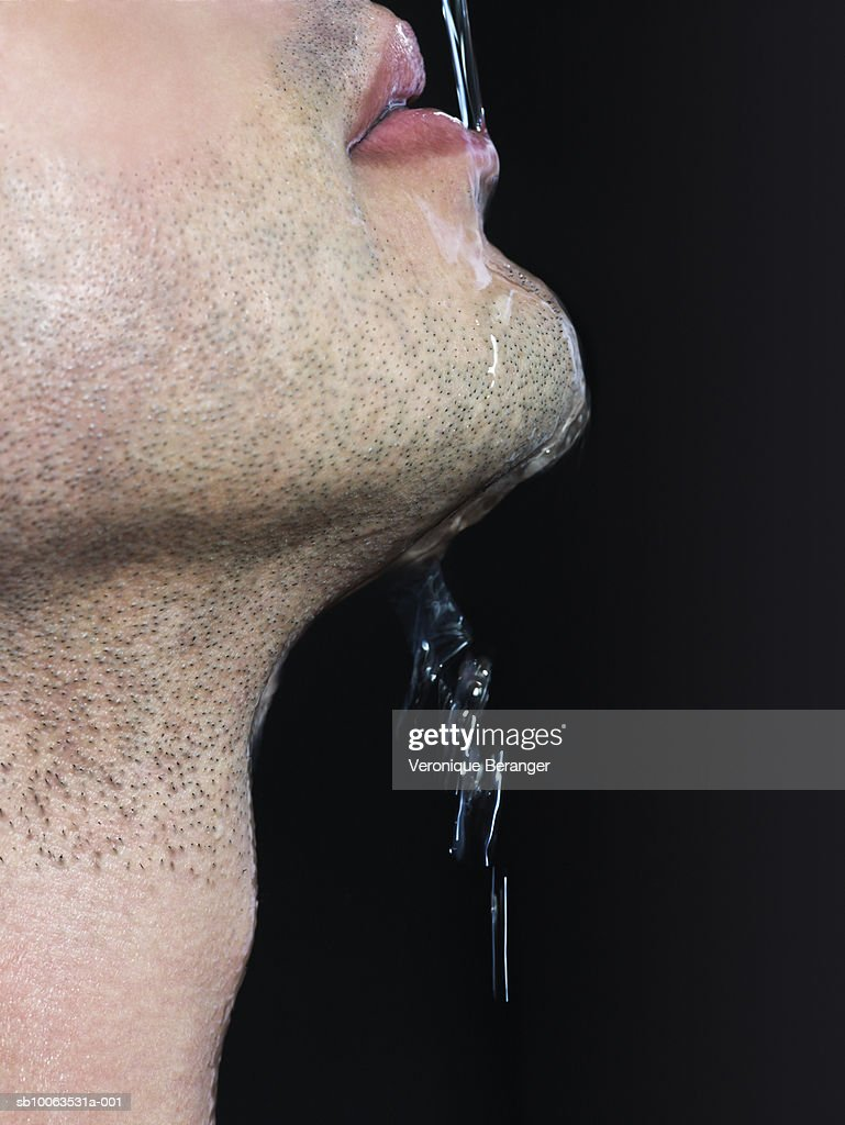 Man with water pouring on mouth, close-up, mid section : Stock Photo