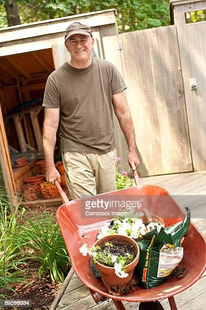 man with wheelbarrel gardening