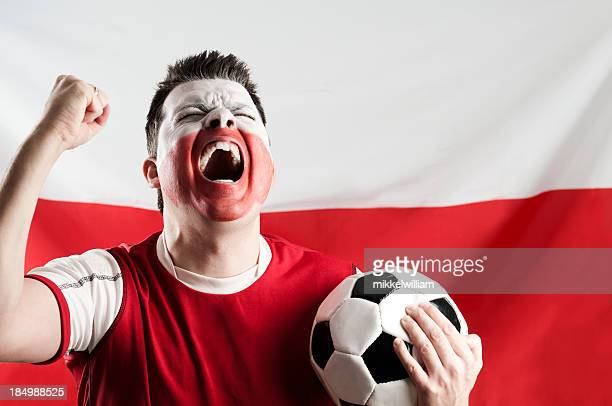 Man with white and red makeup on face holding soccer ball