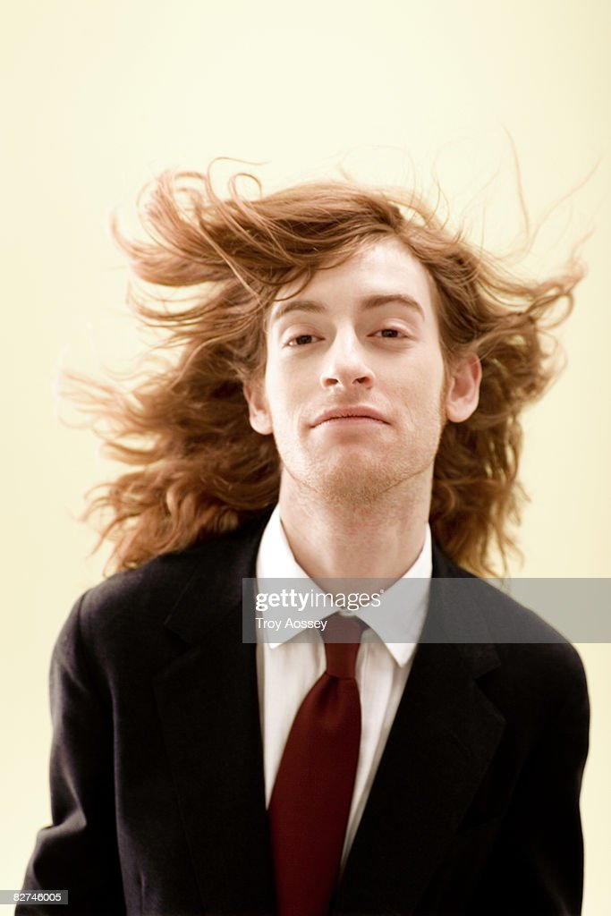man with wind blown hair in business suit  : Stock Photo