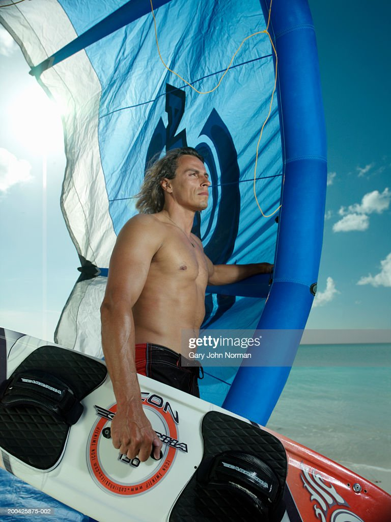 Man with windsurfing gear on beach, side view, close-up