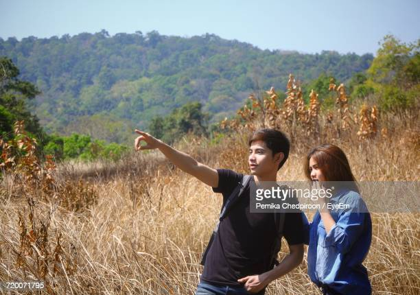 Man With Woman Pointing On Grassy Field