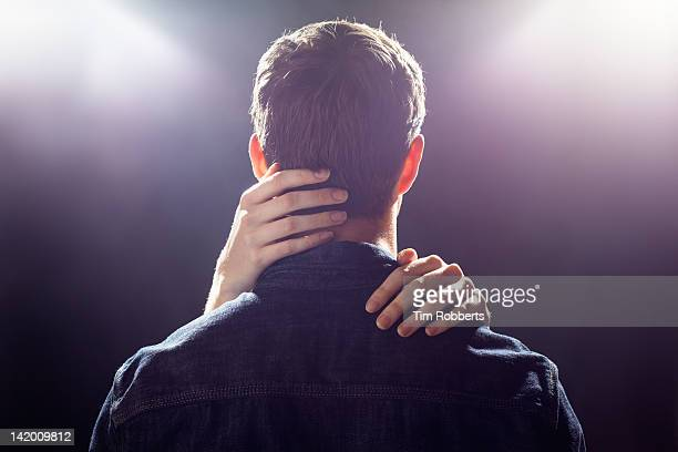 Man with womans hands touching his head.