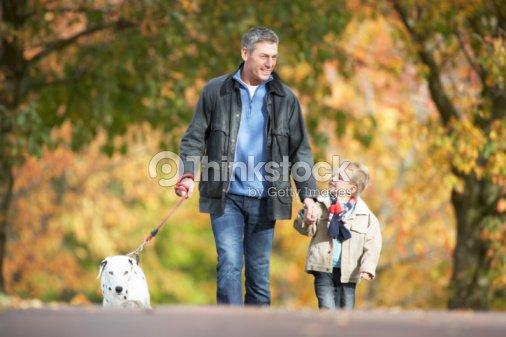 Man With Young Son Walking Dog Through Autumn Park : Foto de stock