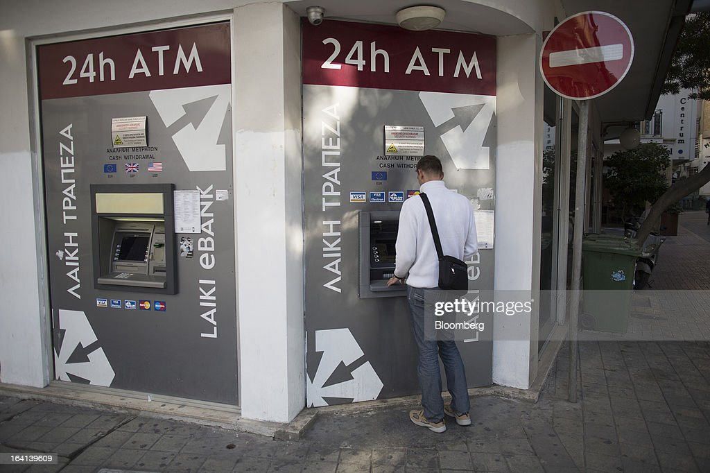A man withdraws cash from an automated teller machine operated by Laiki Bank, also known as Cyprus Popular Bank Pcl, in Nicosia, Cyprus, on Wednesday, March 20, 2013. European policy makers weighed how far to push Cyprus after lawmakers in the Mediterranean nation rejected an unprecedented levy on bank deposits, throwing into limbo a rescue package designed to keep it in the euro. Photographer: Simon Dawson/Bloomberg via Getty Images