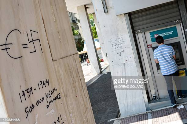 A man withdraws money from an ATM near graffiti reading 'Euro = Swastika 19391944 500000 Greeks dead' in downtown Athens on July 5 2015 Greek voters...
