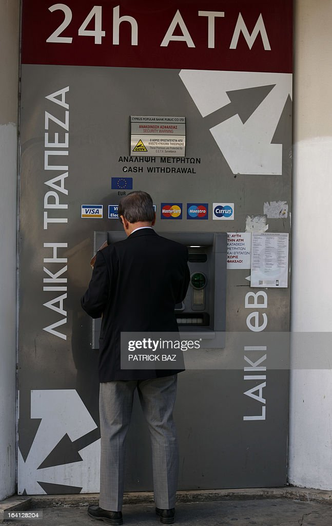 A man withdraws money from the ATM of a Laiki (Popular) Bank branch in central Nicosia on March 20, 2013. Banks have been closed in the east Mediterranean island for the fifth consecutive day as the country was scrambling to secure funding for them after lawmakers rejected last night the terms of an EU bailout deal. AFP PHOTO/PATRICK BAZ