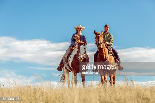 Man Woman And Dog Sitting On Two Horses Outdoors