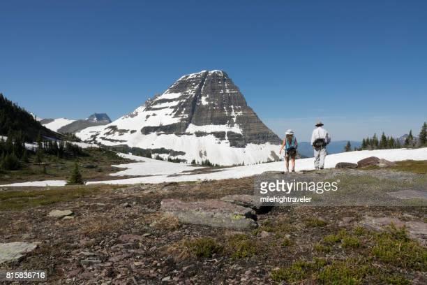 Man woman couple hike Glacier National Park Logan Pass snowfield Bearhat Mountain Montana