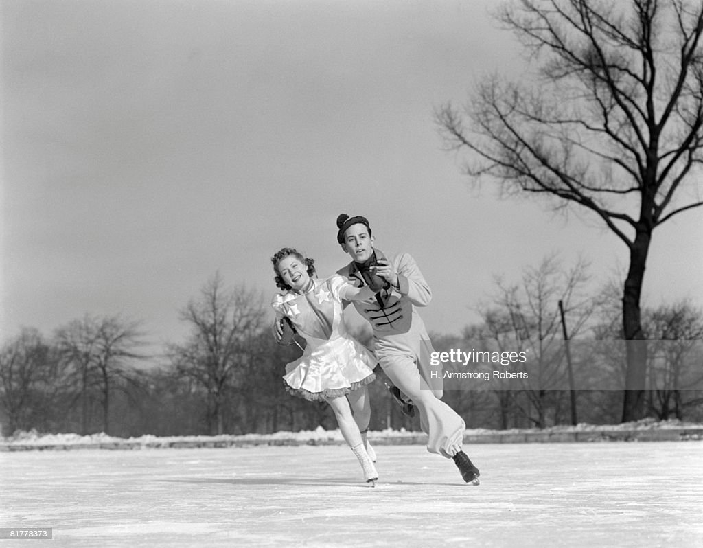 Man Woman Couple Pair Figure Skating On Ice Rink Smiling Costumes Arm In Arm Leaning Precision Glide Dance. : Stock Photo