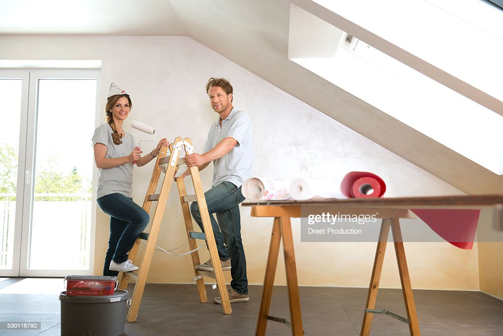 man woman couple renovating home decorating stock photo