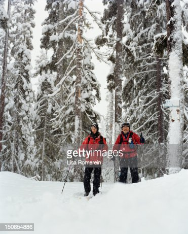 Man & woman cross country skiing in snowy forest : Stock Photo