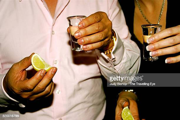Man & woman hands, about to shoot tequila