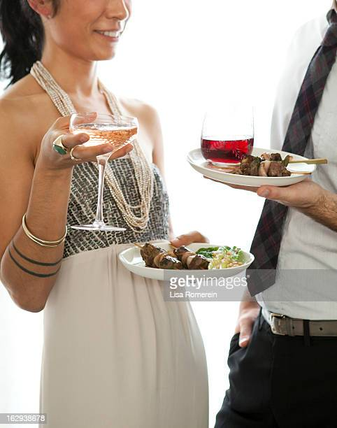 Man & woman talking at party with hors d'oeuvres