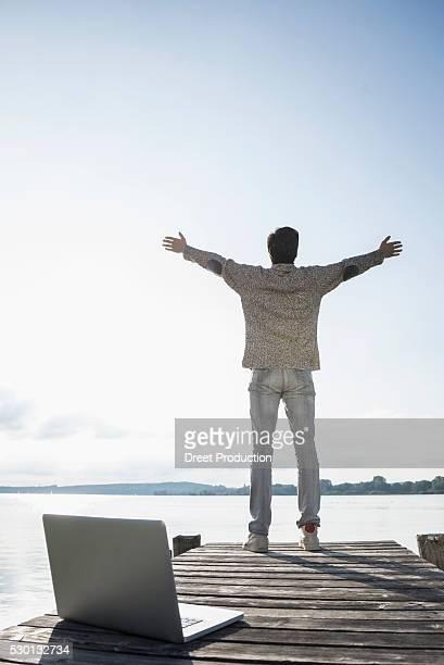 Man wooden jetty working laptop happy