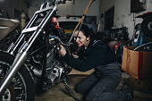 Young man doing hard job in car and motorcycle repair shop.