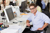 Man Working At Desk In Busy Creative Office Sitting On Chair Smiling To Camera
